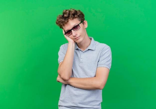 Giovane uomo con gli occhiali neri che indossa la maglietta polo grigia appoggiato la testa sul braccio in attesa sul verde Foto Gratuite