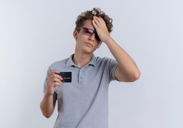 Giovane uomo con gli occhiali neri che indossa la maglietta polo grigia che mostra la carta di credito che sembra in piedi confuso ed ansioso sopra il muro bianco Foto Gratuite