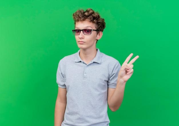 Giovane uomo con gli occhiali neri che indossa la polo grigia che mostra sorridente segno di v sul verde Foto Gratuite
