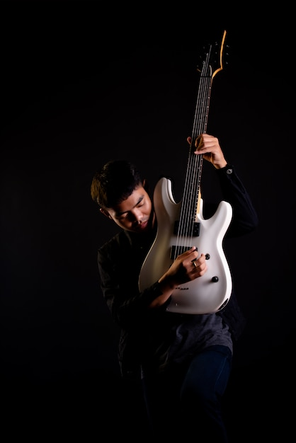 Young man in black leather jacket with electric guitar Free Photo