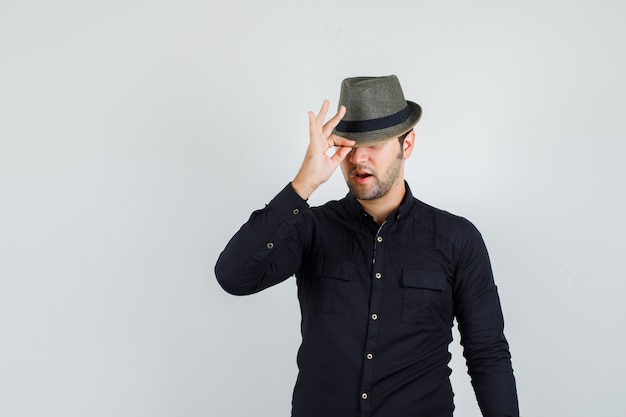 Young man in black shirt pulling down his hat and looking stylish Free Photo