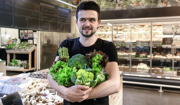 Giovane uomo in maglietta nera che compra solo verdure verdi al mercato Foto Gratuite