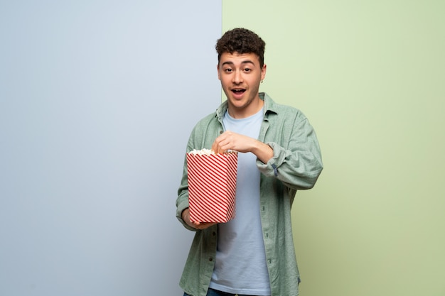 Young man over blue and green  surprised and eating popcorns Premium Photo