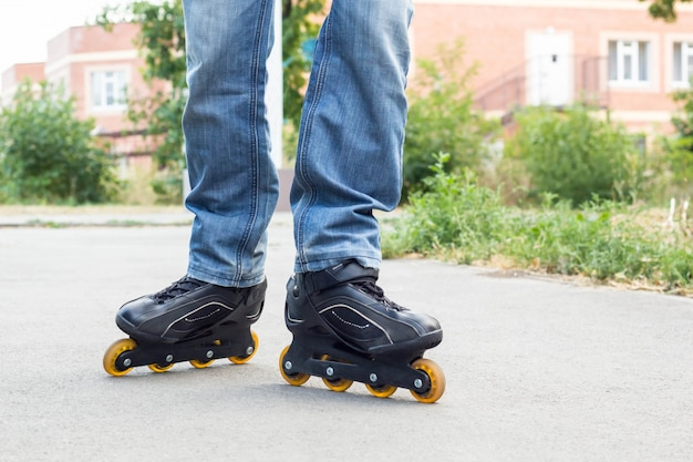 Young man in blue jeans riding roller skates in the city. close up legs Premium Photo