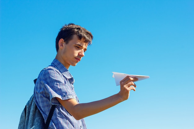 A young man on a blue sky holding a paper plane Premium Photo