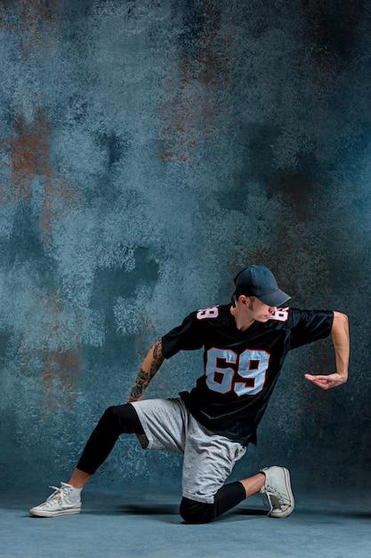 Young man break dancing on wall wall. Free Photo