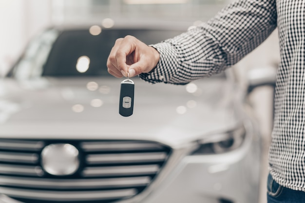 Young man buying new car at the dealership Premium Photo