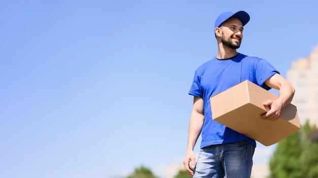 若い男が配達小包を運ぶ Premium写真