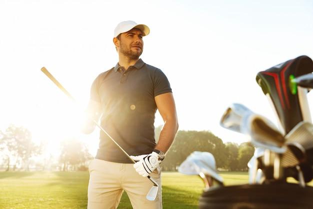 Молодой человек, несущий гольф-клуб, стоя на поле Бесплатные Фотографии