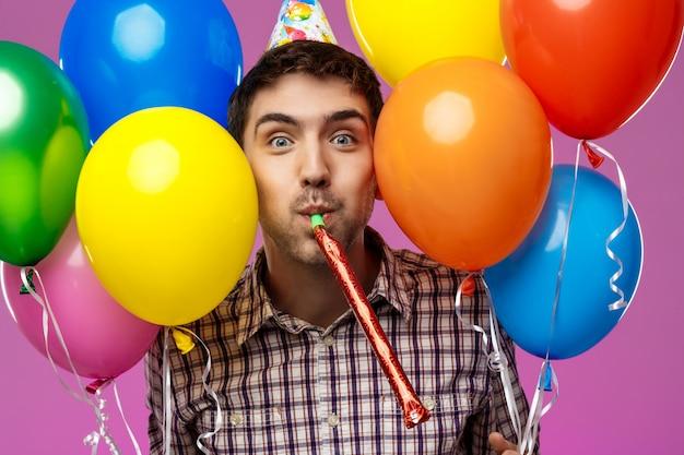 젊은이 생일 축 하, 보라색 벽 위에 다채로운 Baloons를 들고. 무료 사진