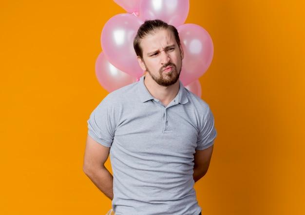 オレンジ色の壁の上に立って不機嫌と不幸を脇に見て風船の束を保持している誕生日パーティーを祝う若い男 無料写真