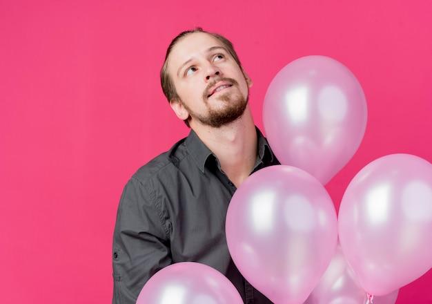 ピンクの壁の上に立って物思いにふける表情で見上げる風船の束を保持している誕生日パーティーを祝う若い男 無料写真