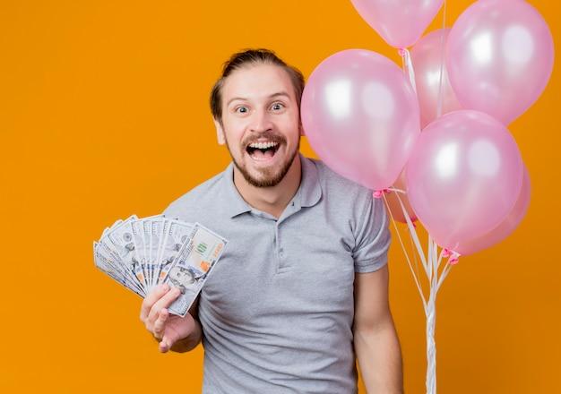 オレンジ色の壁の上に立って幸せで興奮した現金を示す風船の束を保持している誕生日パーティーを祝う若い男 無料写真