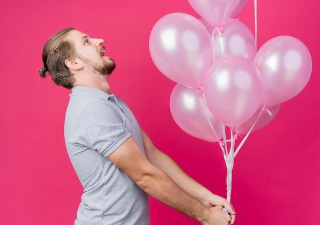 ピンクの壁に幸せで興奮して見上げる横に立っている風船の束を保持している誕生日パーティーを祝う若い男 無料写真
