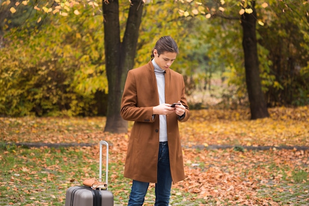 Young man checking his phone in the park Free Photo