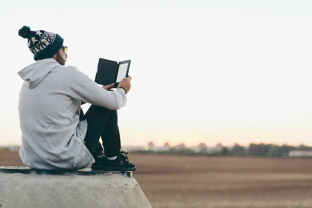 Young man chilling with tablet on nature Free Photo
