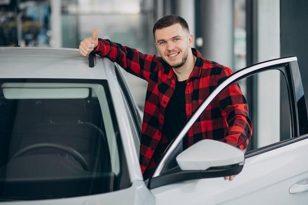 Молодой человек выбирая автомобиль в автосалоне Бесплатные Фотографии