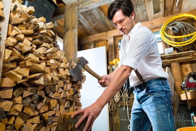 Young man chopping fire wood in mountain chalet Premium Photo