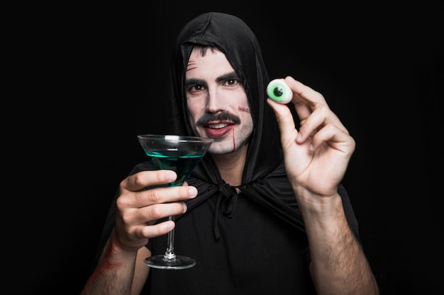 Young man in cloak posing in studio with artificial eye and green beverage Free Photo