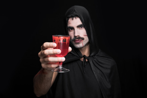 Young man in cloak with hood posing in studio with glass of red liquid Free Photo
