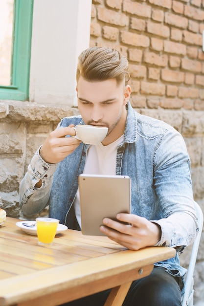 Young man in coffee shop cafe using a tablet. Premium Photo