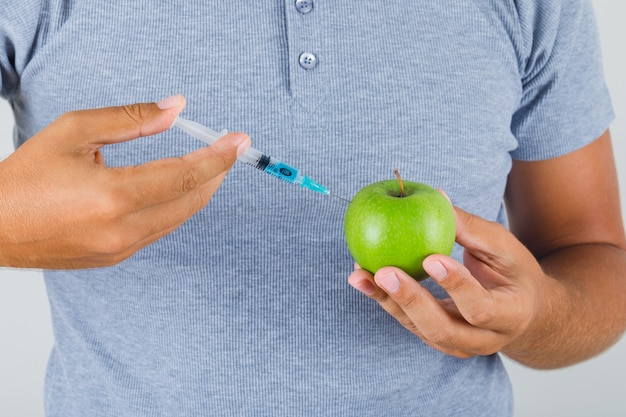若い男が灰色のtシャツでリンゴに注射によって実験を実施 無料写真