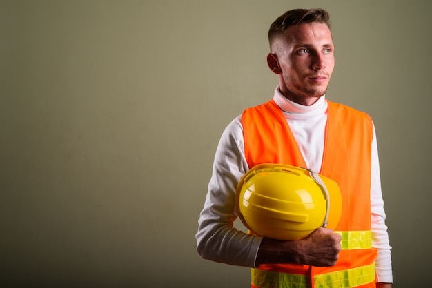 Молодой человек на стройке у цветной стены Premium Фотографии