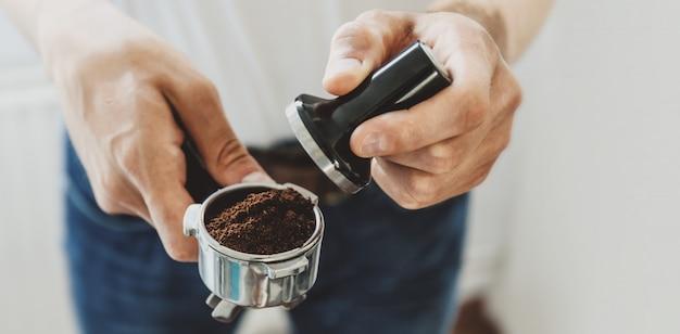 若い男が自宅で自動coffeemachineでコーヒーを調理します。水平。バナー。 無料写真