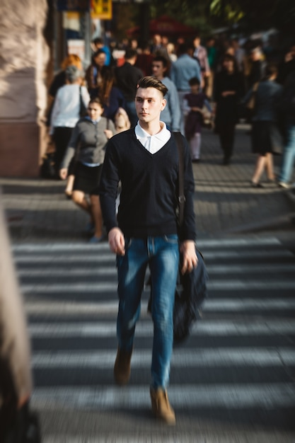 Young man cross the street Free Photo