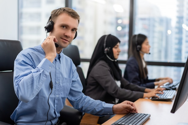 Young man customer service agent with headsets working on computer in a call centre Premium Photo