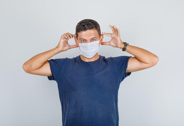 Giovane uomo in maglietta blu scuro che indossa maschera medica e guardando attento, vista frontale. Foto Gratuite