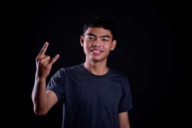 Young man in dark t shirt making a rocker gesture Free Photo