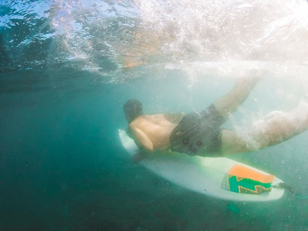 Young man diving with surfboard underwater Free Photo