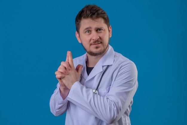 Доктор молодого человека нося белое пальто и стетоскоп держа символическое оружие с жестом рукой над изолированной голубой предпосылкой Бесплатные Фотографии