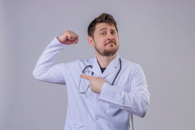 Пальто и стетоскоп доктора молодого человека нося белые указывая палец к его выражению прочности бицепса, концепции победителя Бесплатные Фотографии