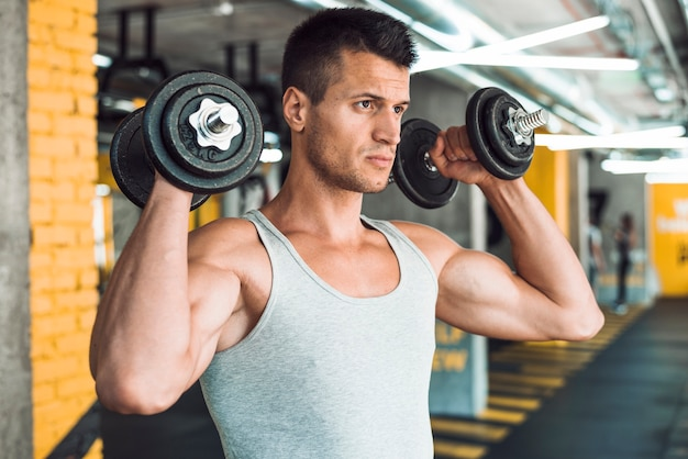 Young man doing exercise with dumbbells strengthening his shoulder 23 2147949574