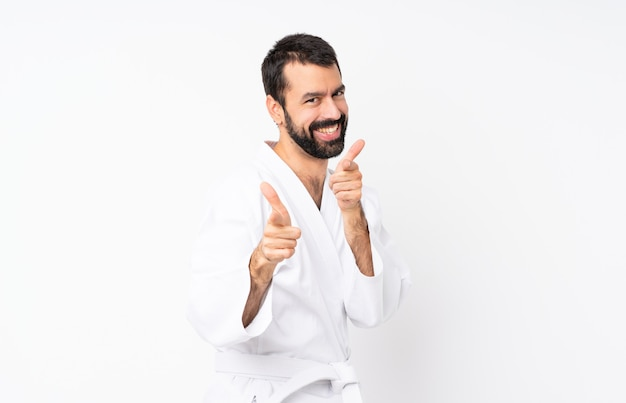 Young man doing karate over isolated white pointing to the front and smiling Premium Photo