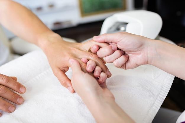 Giovane uomo che fa manicure in salone. concetto di bellezza. Foto Gratuite
