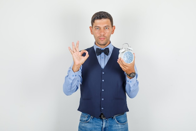 Young man doing ok sign with alarm clock in suit, jeans and looking pleased. Free Photo
