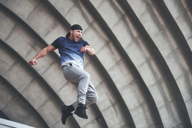 Молодой человек делает прыжок паркура в городском пространстве в солнечный весенний летний день города. Бесплатные Фотографии