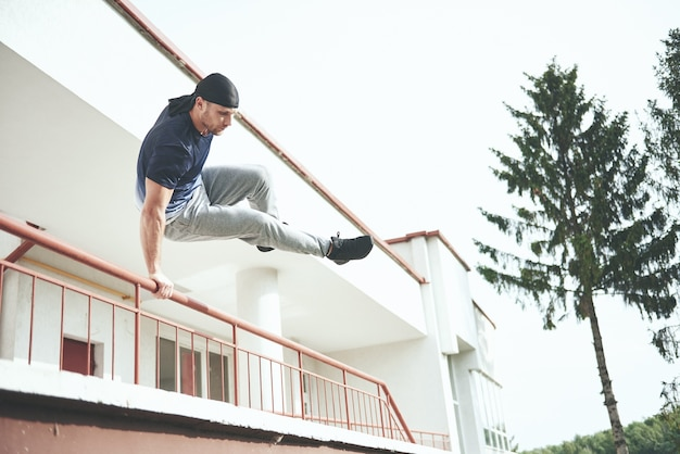 Young man doing parkour jump in urban space in the city sunny spring summer day. Free Photo