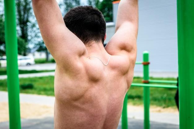Молодой человек делает подтягивания на турнике на открытом воздухе на спортивной площадке. уличные тренировки. Premium Фотографии