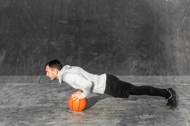 Молодой человек делает отжимания на баскетбол Бесплатные Фотографии