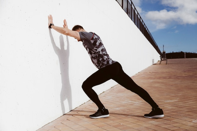 Young man doing standing wall push up Free Photo