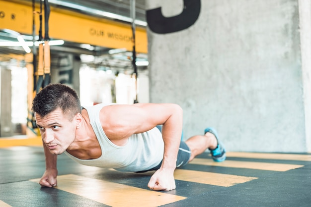 Young man doing workout in fitness club Free Photo