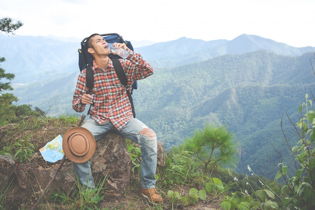 Young man drank water on a hilltop in a tropical forest along with backpacks in the jungle. adventure, hiking Free Photo