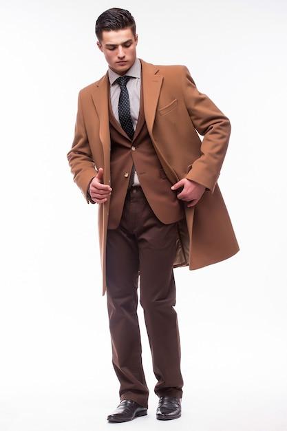 Il giovane si è vestito in cappotto isolato sopra la parete bianca Foto Gratuite