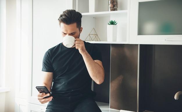 黒い服を着て携帯電話でチャットしながらキッチンでコーヒーを飲む若い男 Premium写真