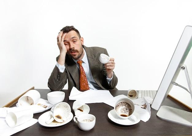 Молодой человек пьет много кофе, но все равно не может проснуться и работать. продолжайте спать в офисе. понятие проблем офисного работника, бизнеса, проблем и стресса. Бесплатные Фотографии