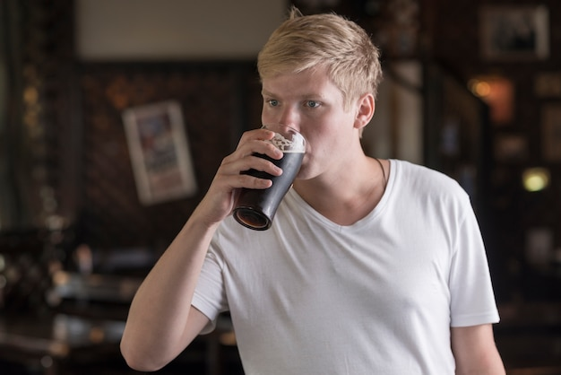 Young man drinking beer in pub Free Photo